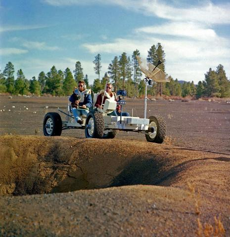 Two men test drive rover on artificial crater field.