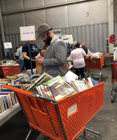 A patrol fills a shopping cart with dozens of books at the 63rd Annual VNSA Book Fair.