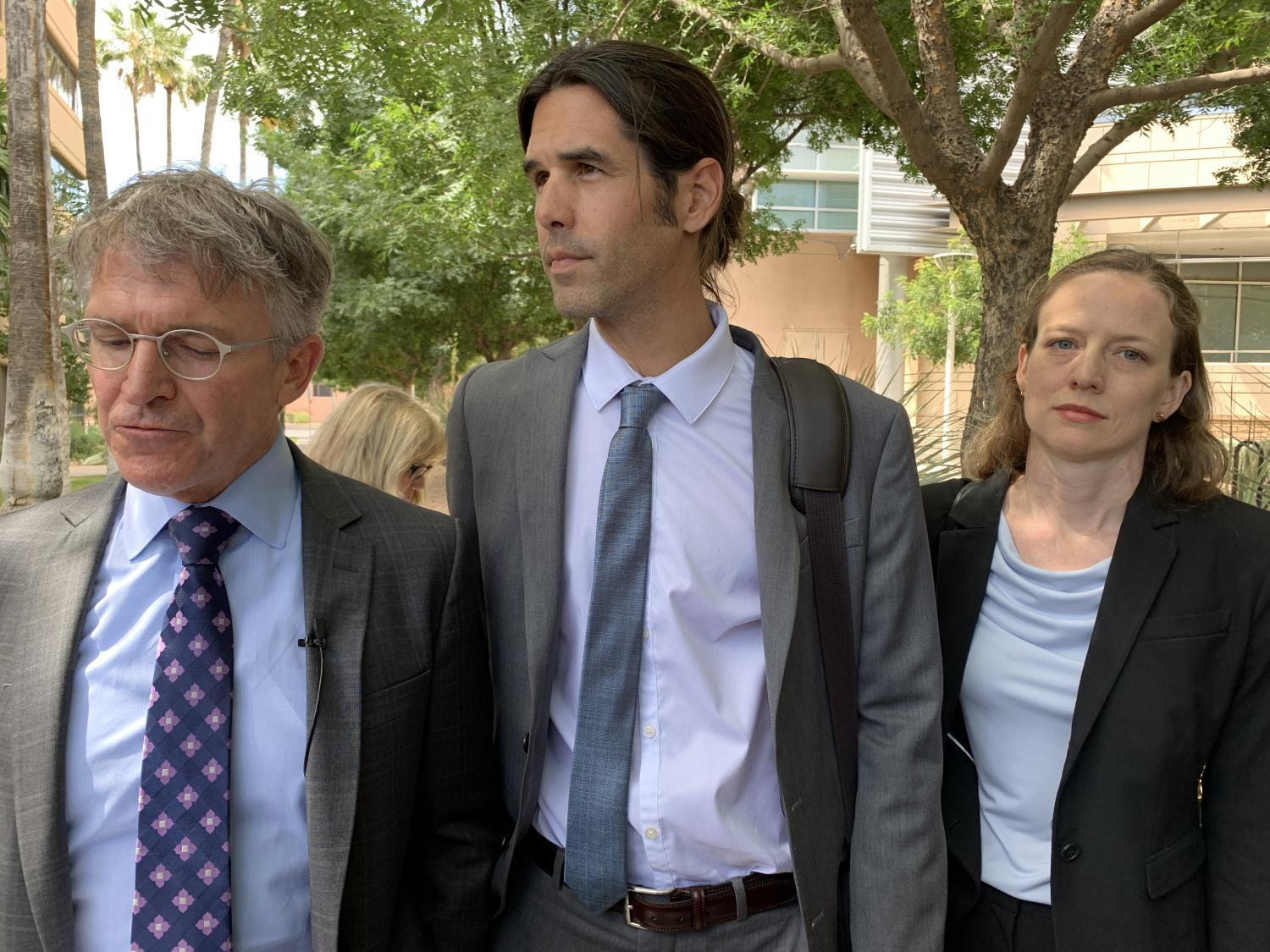 Scott Warren, center, flanked by his attorneys