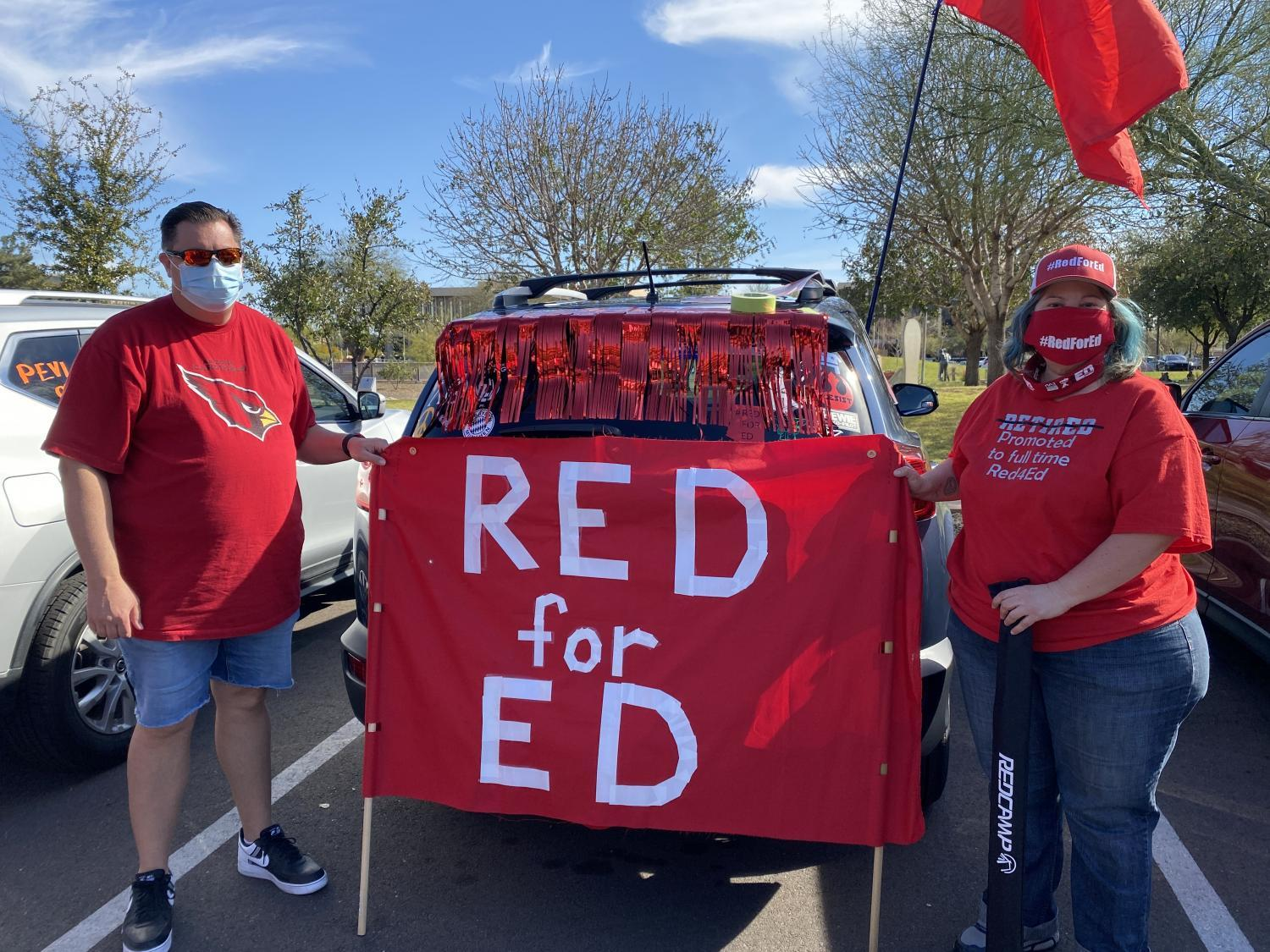 People hold up a sign that reads Red for Ed