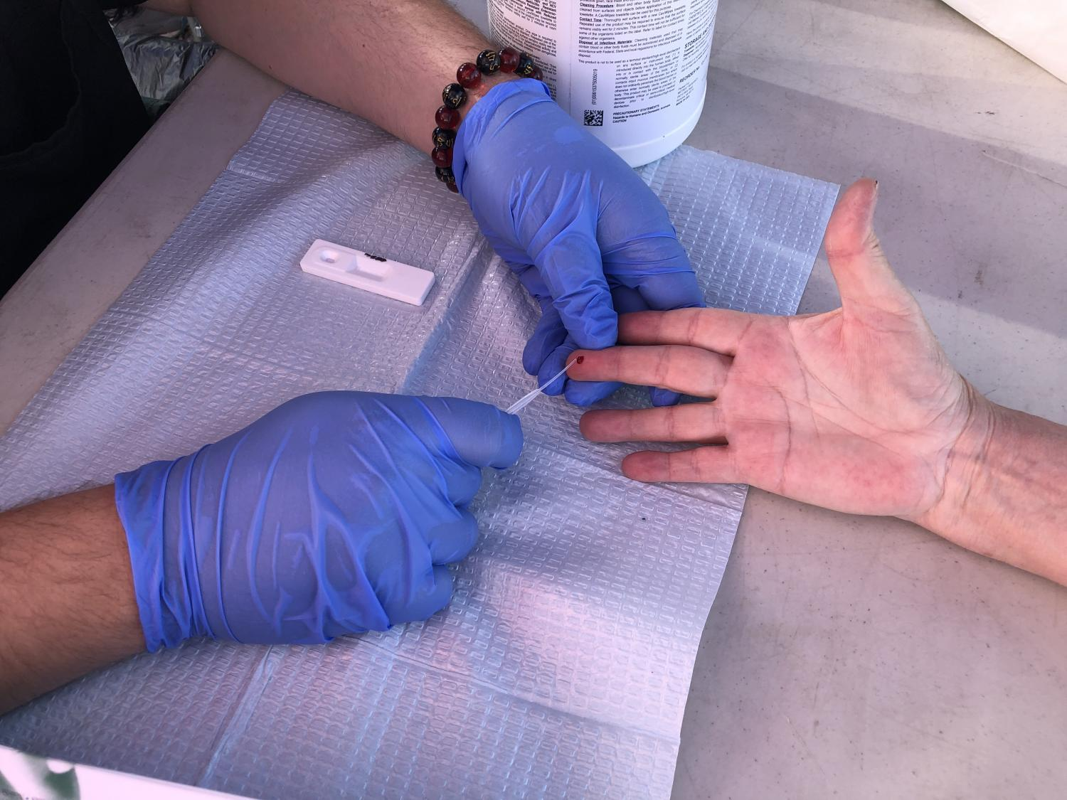 A woman gets her finger pricked for a coronavirus antibody test.