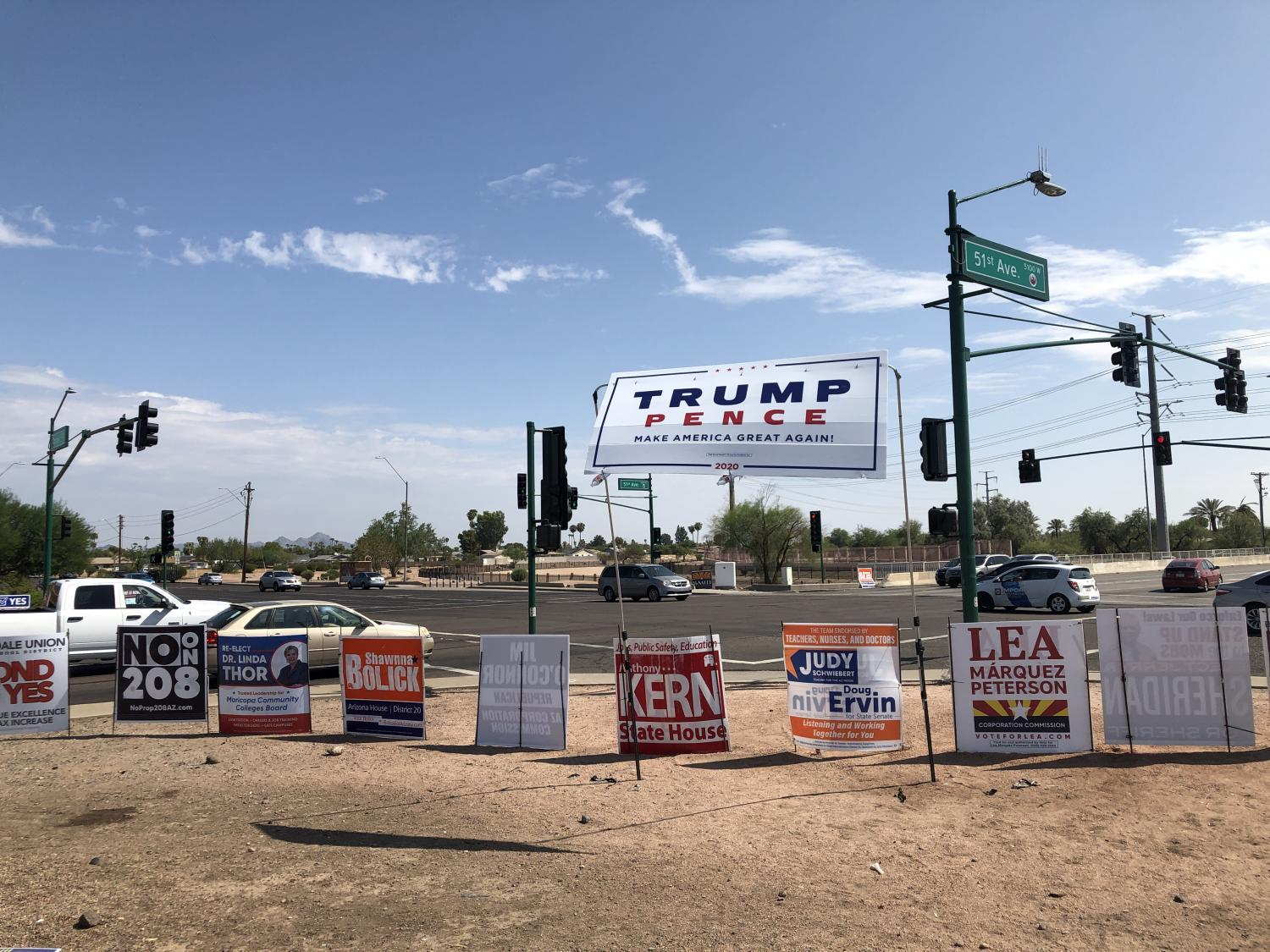 A large Trump/Pence sign mounted above other signs in north Phoenix.