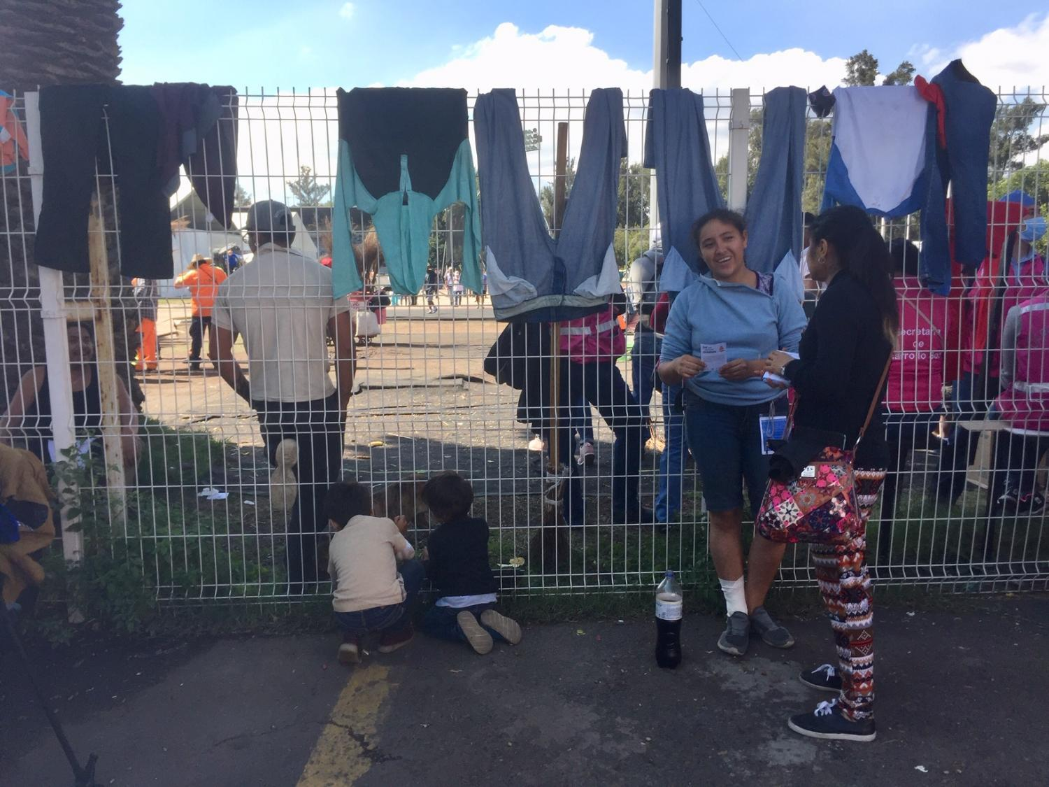 Migrants wait and dry clothes at the gate of the shelter in Mexico City.