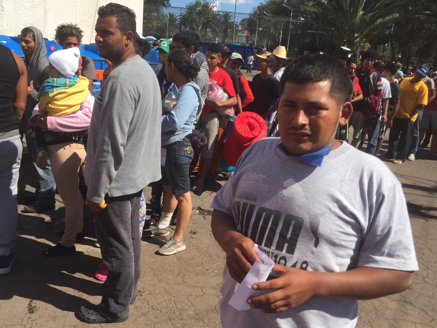 Migrants from the caravan wait on line to get their lunch at the shelter in Mexico City.