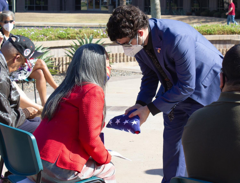 A representative from Congressman Raul Grijalva hands a folded flag to Rose Biggs-Dickerson.
