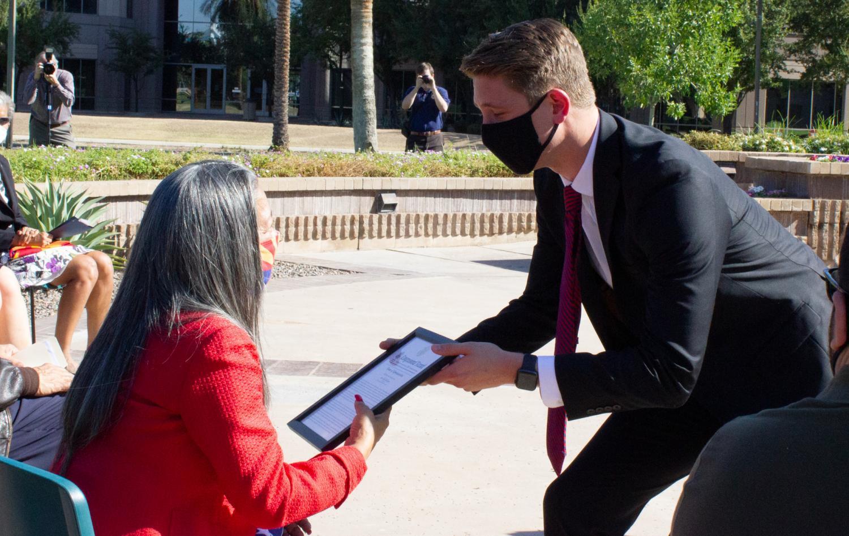 A representative from Congressman Greg Stanton presents a Congressional Record to Rose Biggs-Dickerson.