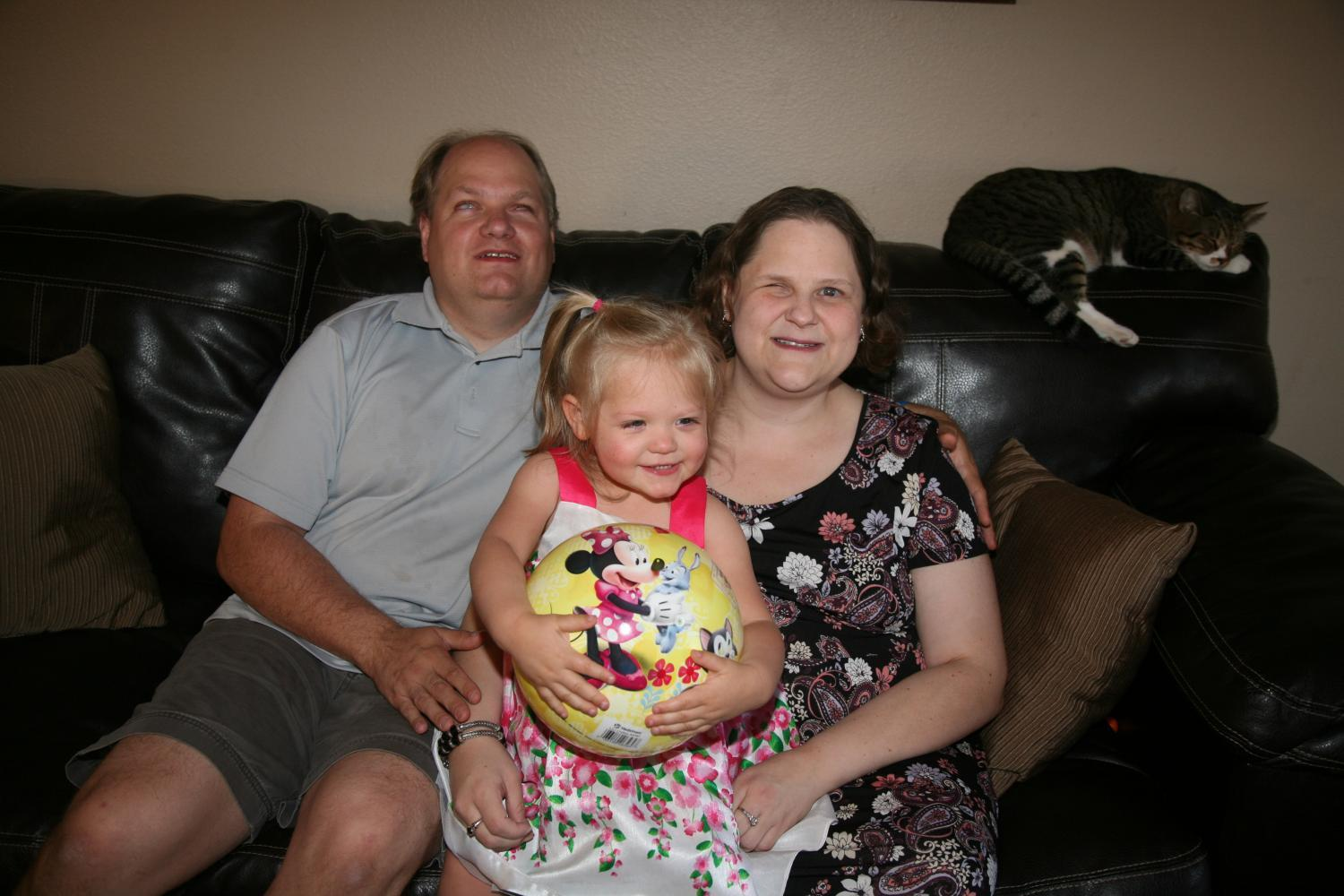 Darrell and Allison Hilliker sit with their 2-year-old daughter, Allyssa, and their cat, Chaos, on their couch.