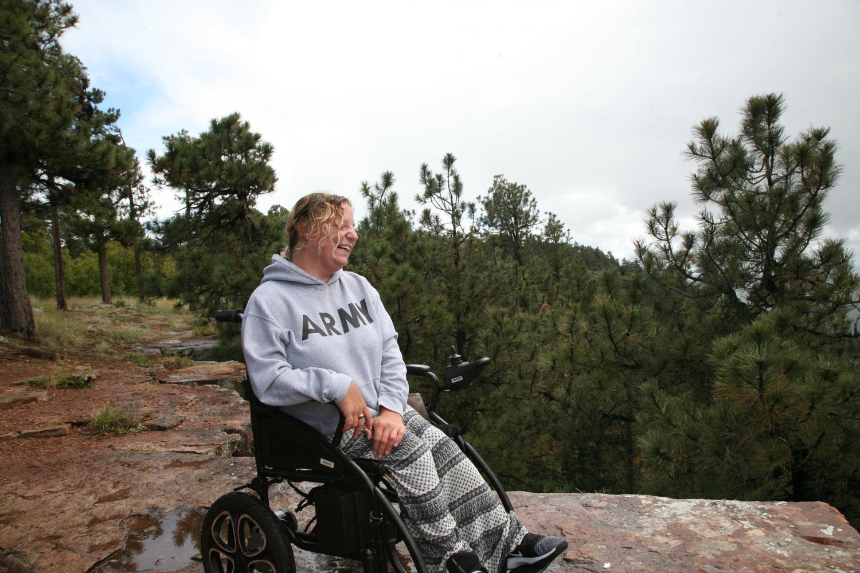 Carly Verbeke laughing in a wheelchair near the edge of the Mogollon Rim