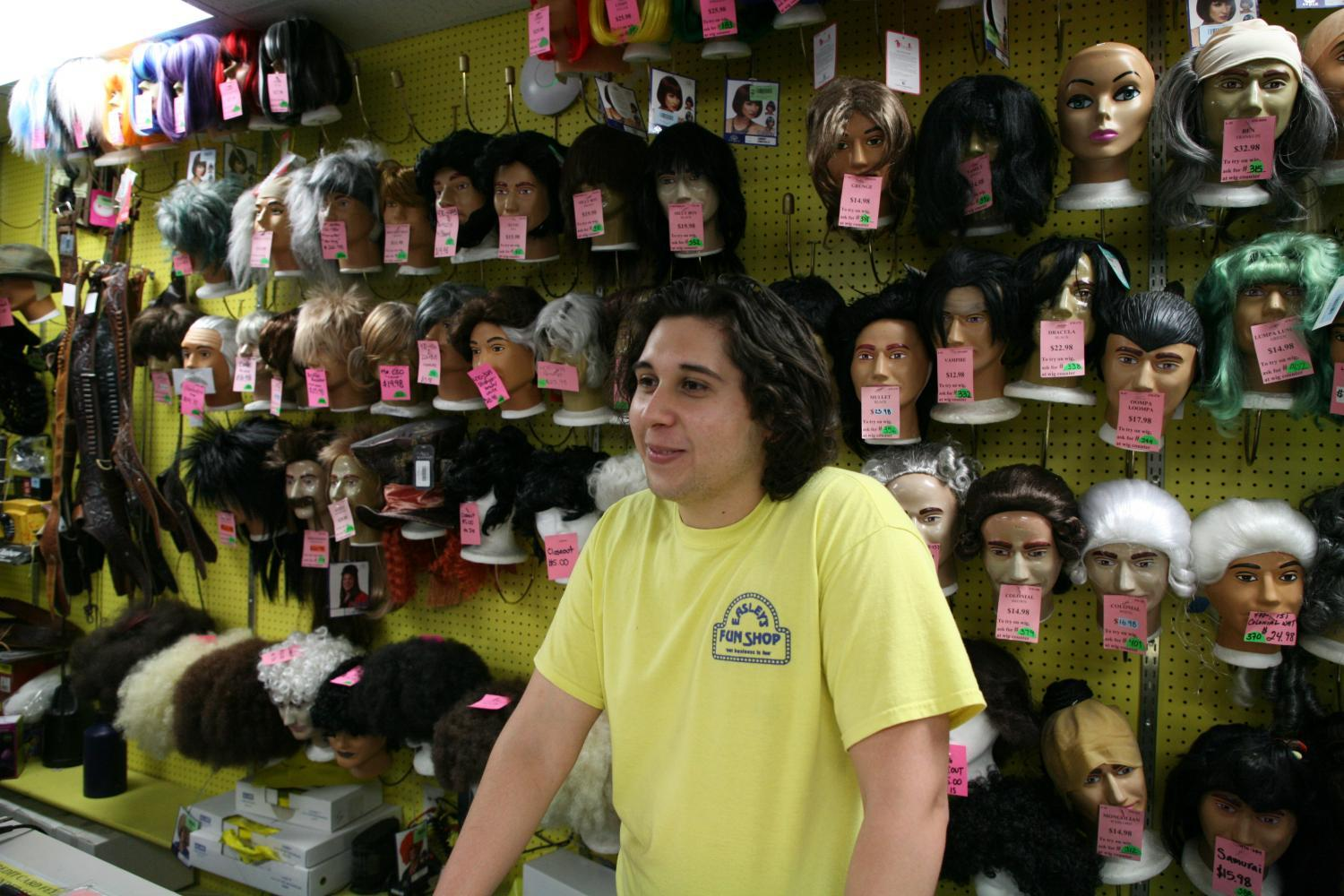Mike Hernandez stands in front rows of wigs at Easley