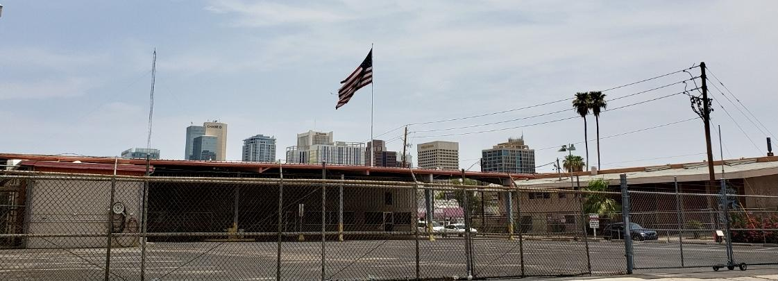 flag flying with downtown skyline in the back