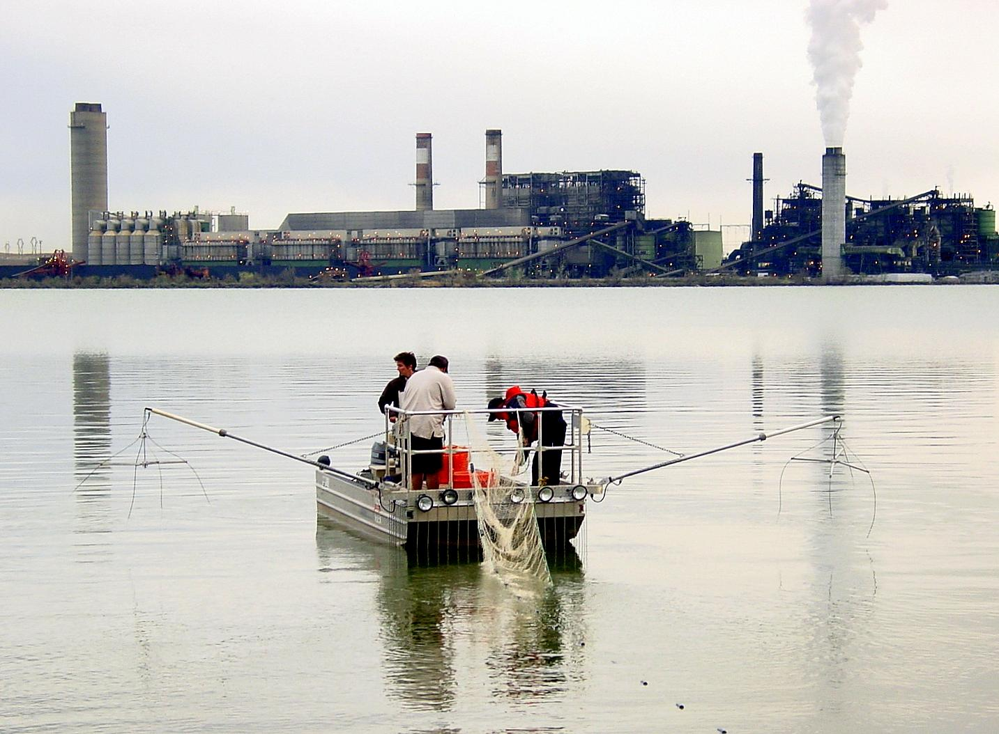 Three people on a small boat in a lake next to a power plant.