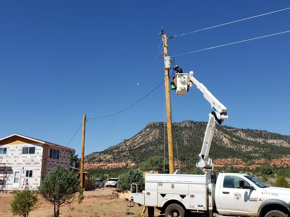 A Navajo Tribal Utility Authority crew works to connect a home to the electric grid