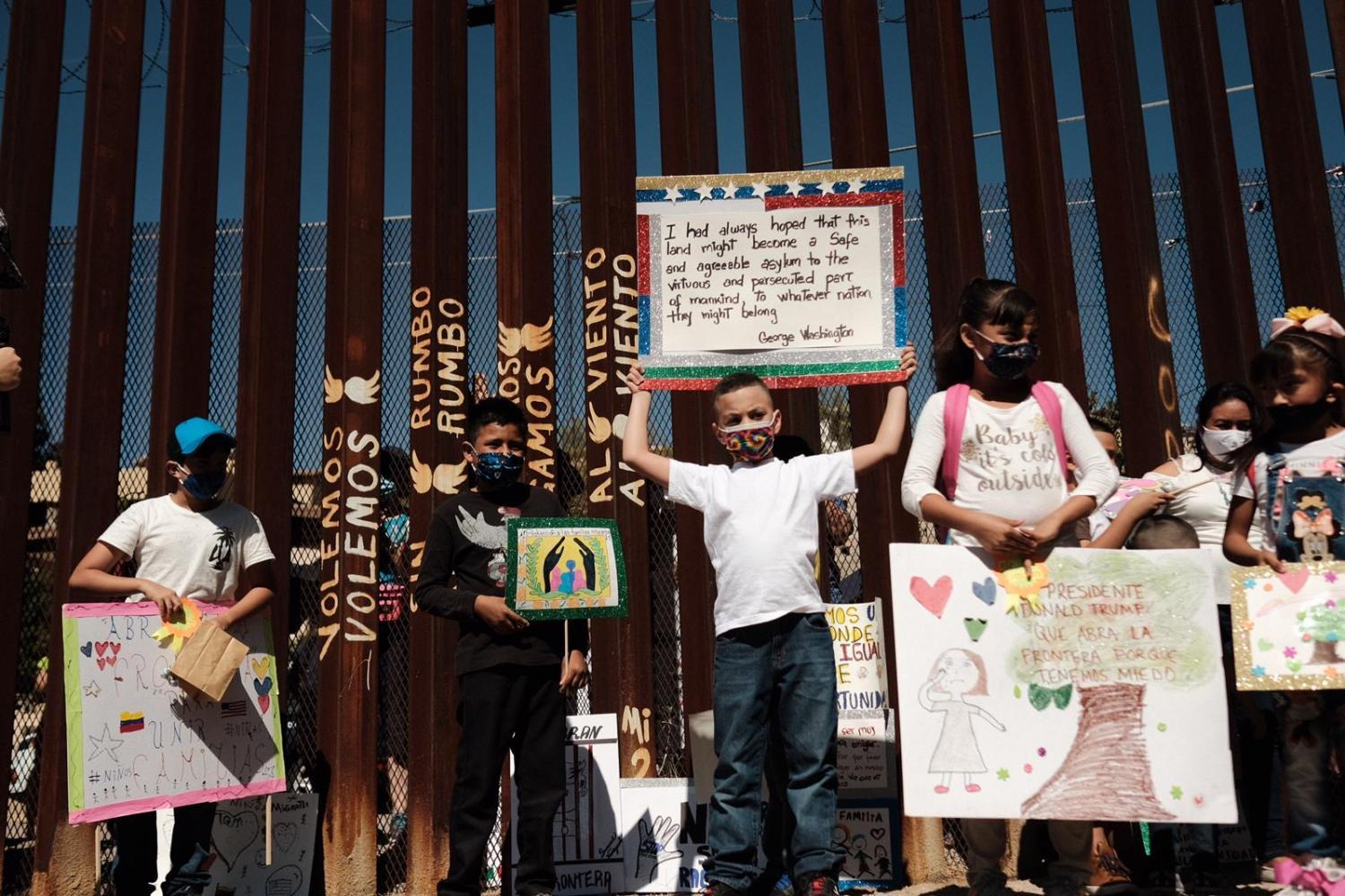 asylum seekers hold up signs