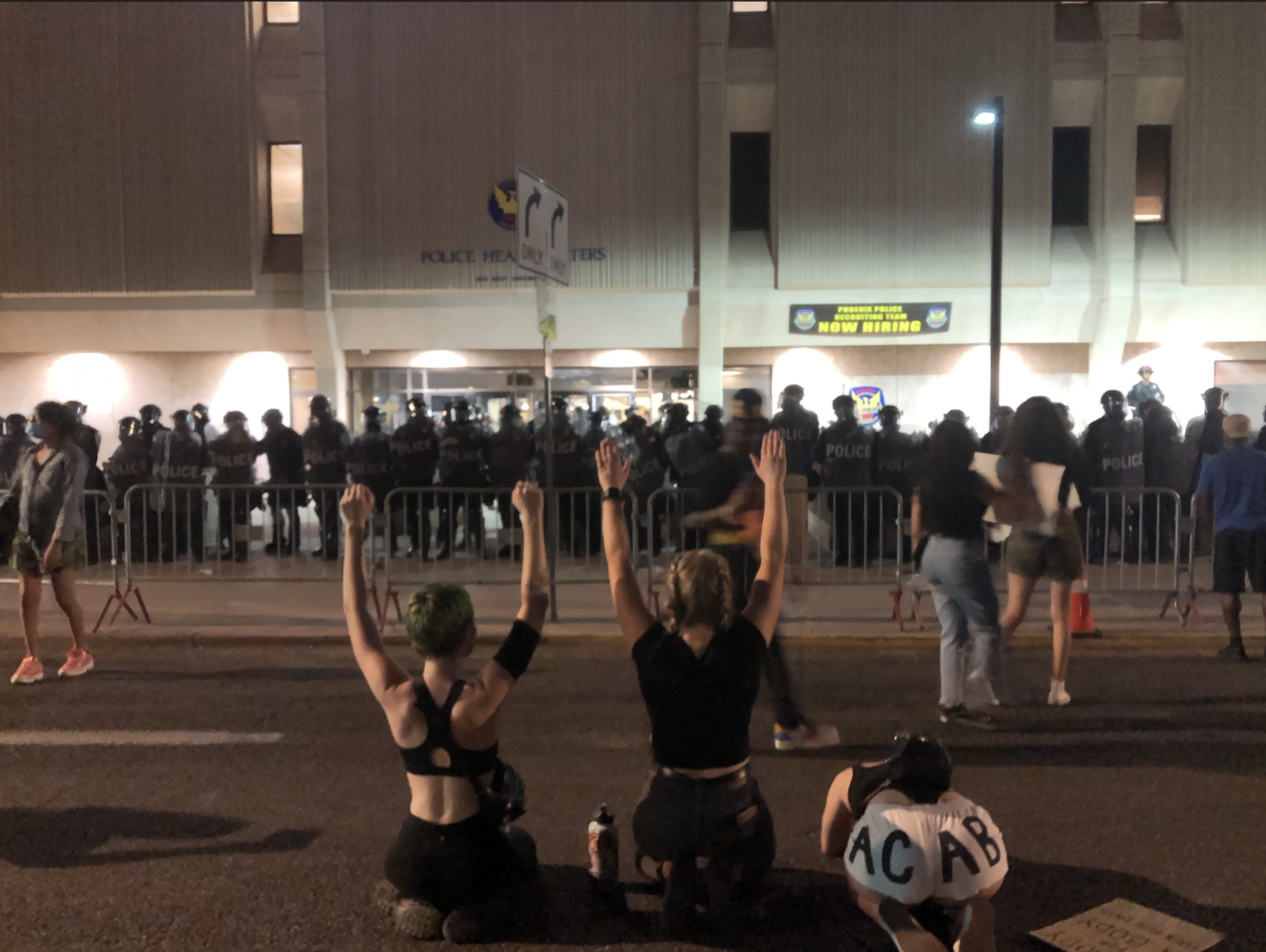 Protesters kneel with their hands in the air in front of Phoenix Police headquarters.