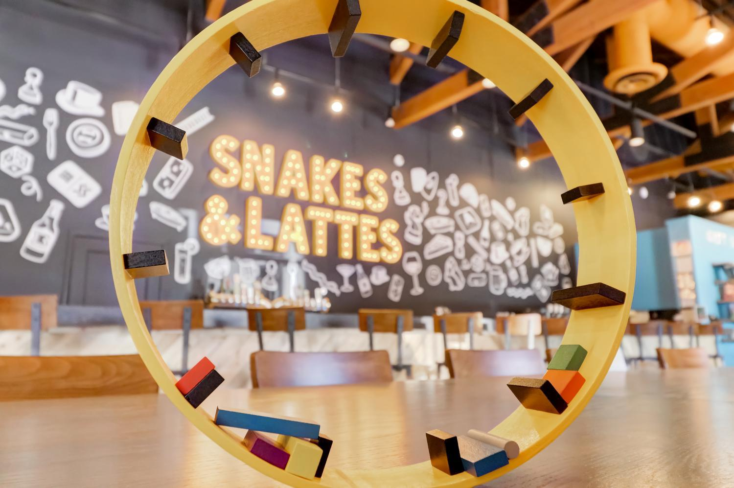 sign says snakes & lattes on wall surrounded by games and seats