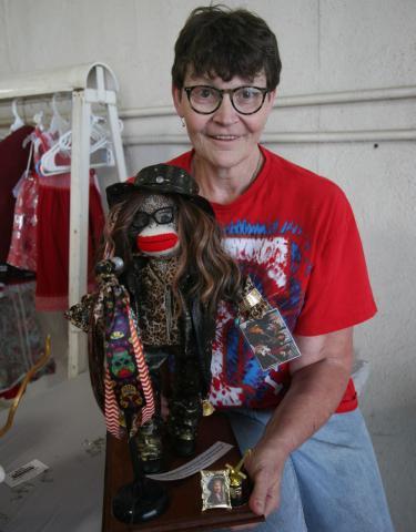 Angela eshelman holds a sock monkey dressed like steven tyler