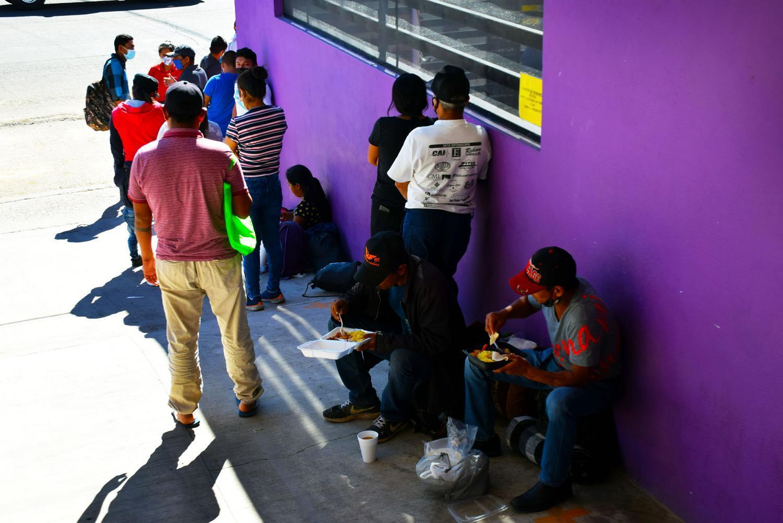 Migrants wait outside KBI