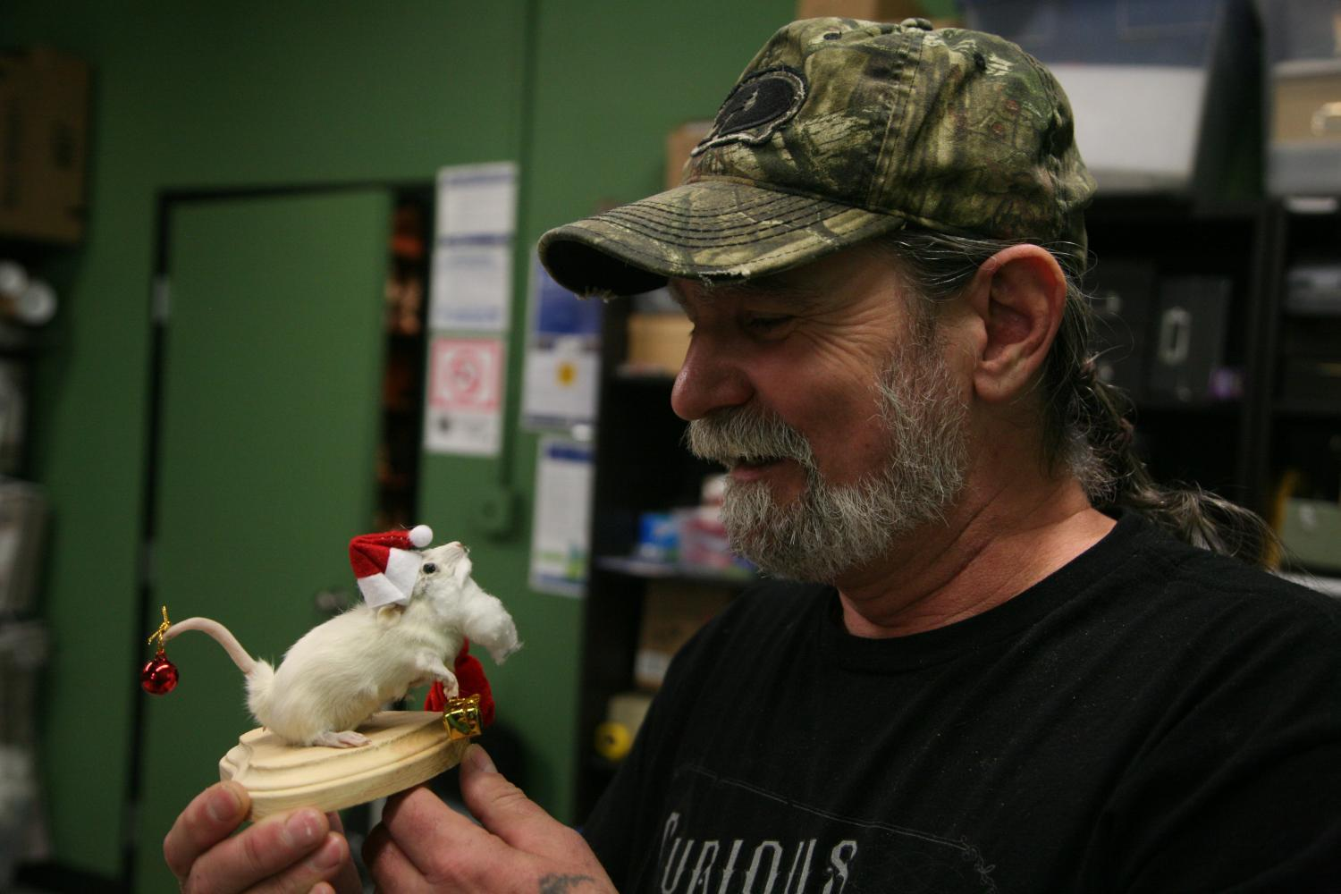 teacher doug james holds a taxidermied rat dressed like santa