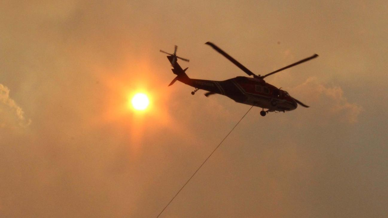 A helicopter supports efforts of ground firefighters