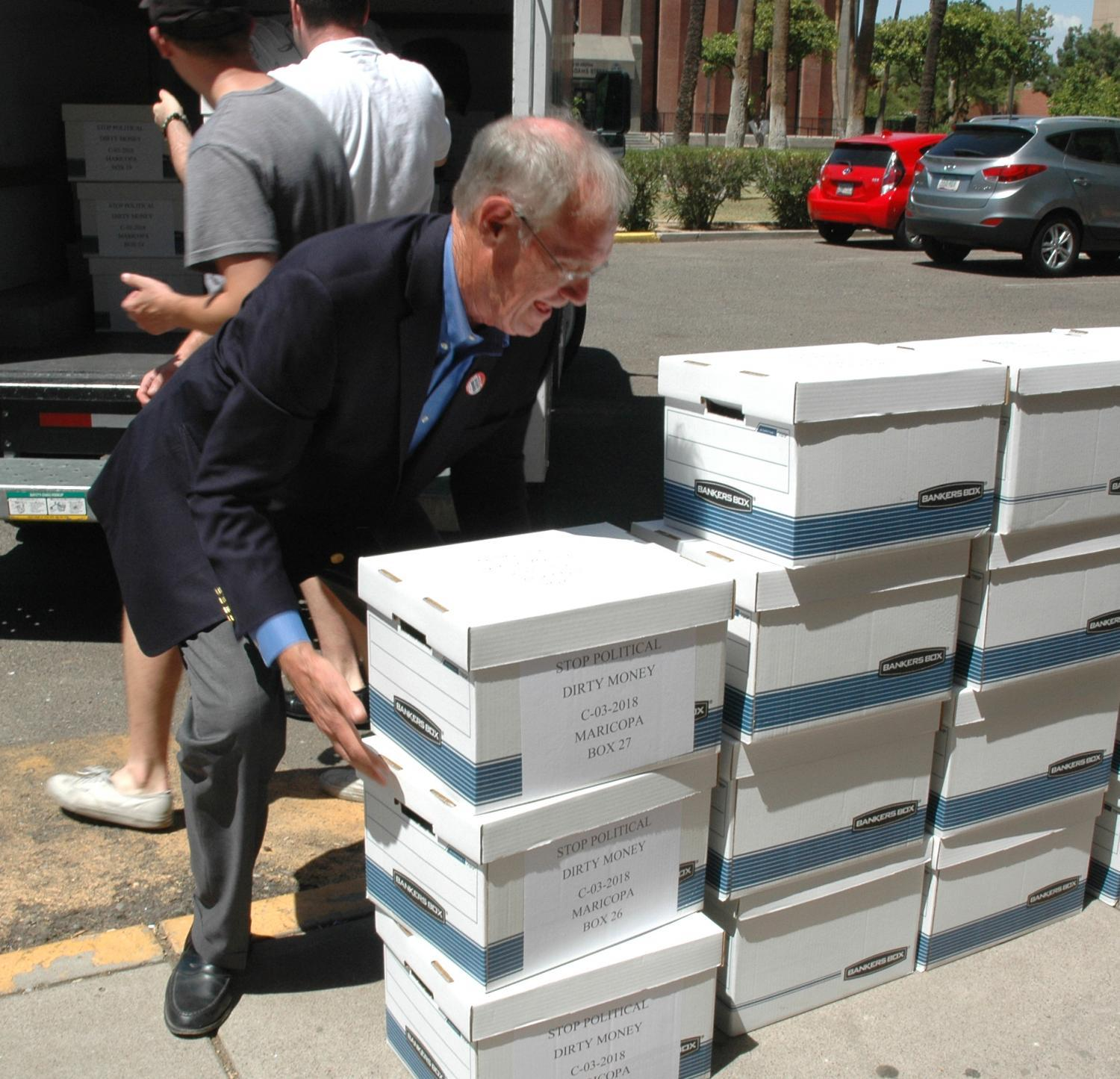 Terry Goddard bends down to lift a box of signatures