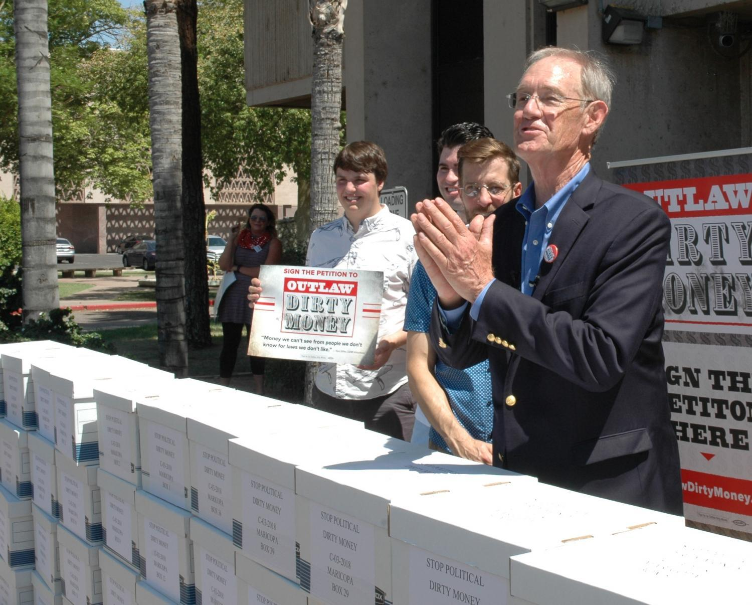 Terry Goddard stands behind a row of boxes containing signatures. Supporters with signs stand behind him.