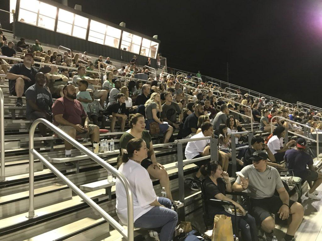 Fans in bleachers at a football game between Phoenix and Scottsdale Colleges.