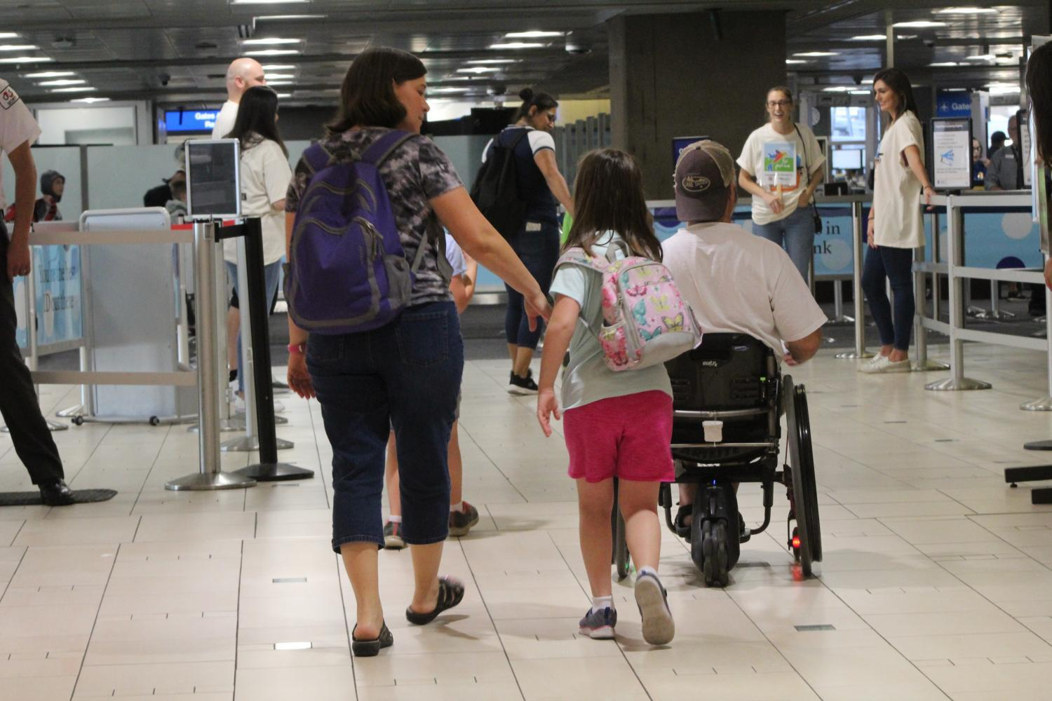 Lisa Celano goes through security with her 11-year-old twins who have Down syndrome and autism.