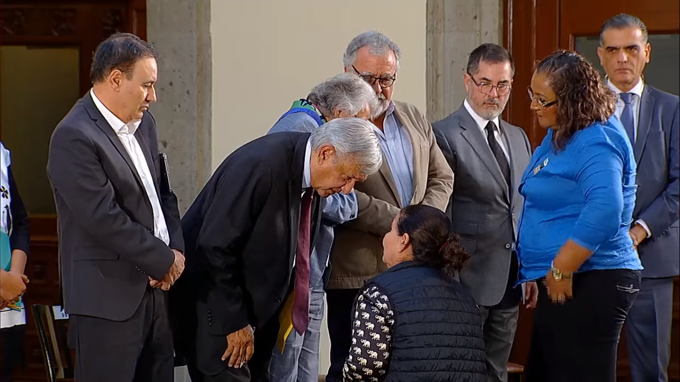 Maria Isela Valdez Chaidez kneels before President Andres Manuel Lopez Obrador and asks for help finding her missing son.