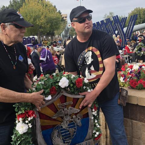 Two men present a wreath at a Pearl Harbor remembrance ceremony at the Arizona state Capitol, Dec. 7, 2019.
