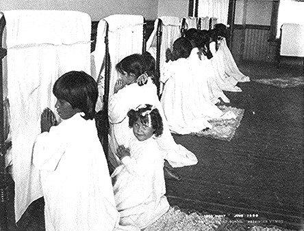 Young girls praying beside their beds at Phoenix Indian School