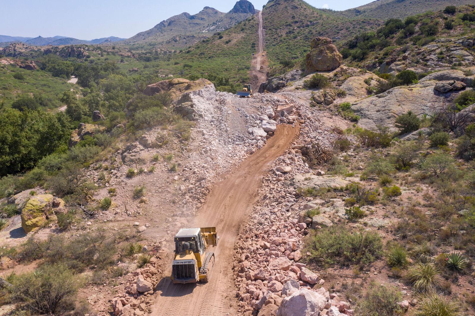 Border wall bulldozer mountains John Kurc