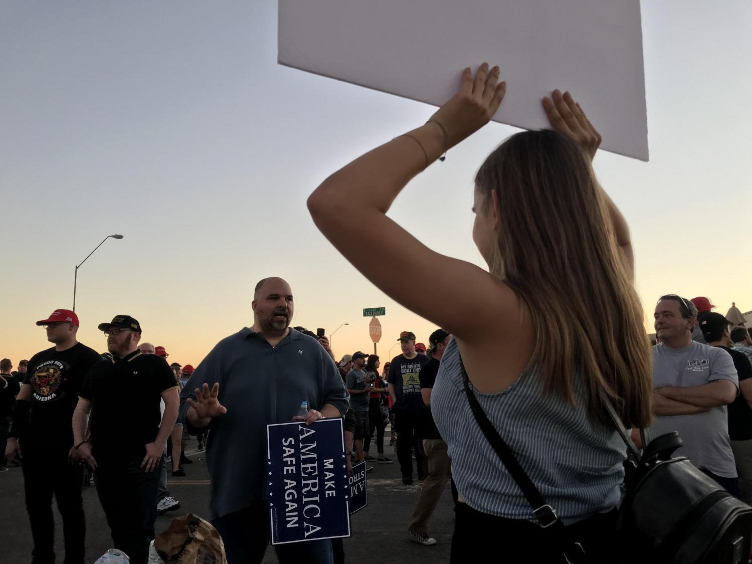 A Trump supporter and protester debate political issues outside the hangar where Trump was speaking in Mesa.
