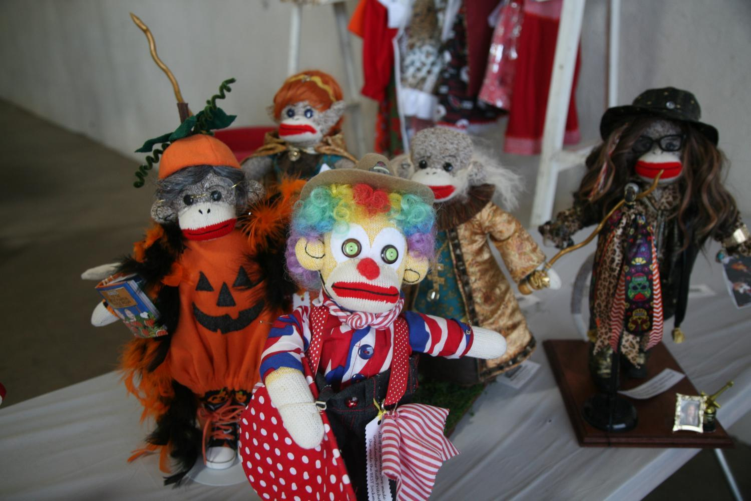several sock monkeys, one dressed like a pumpkin, a rodeo clown and fantasy characters