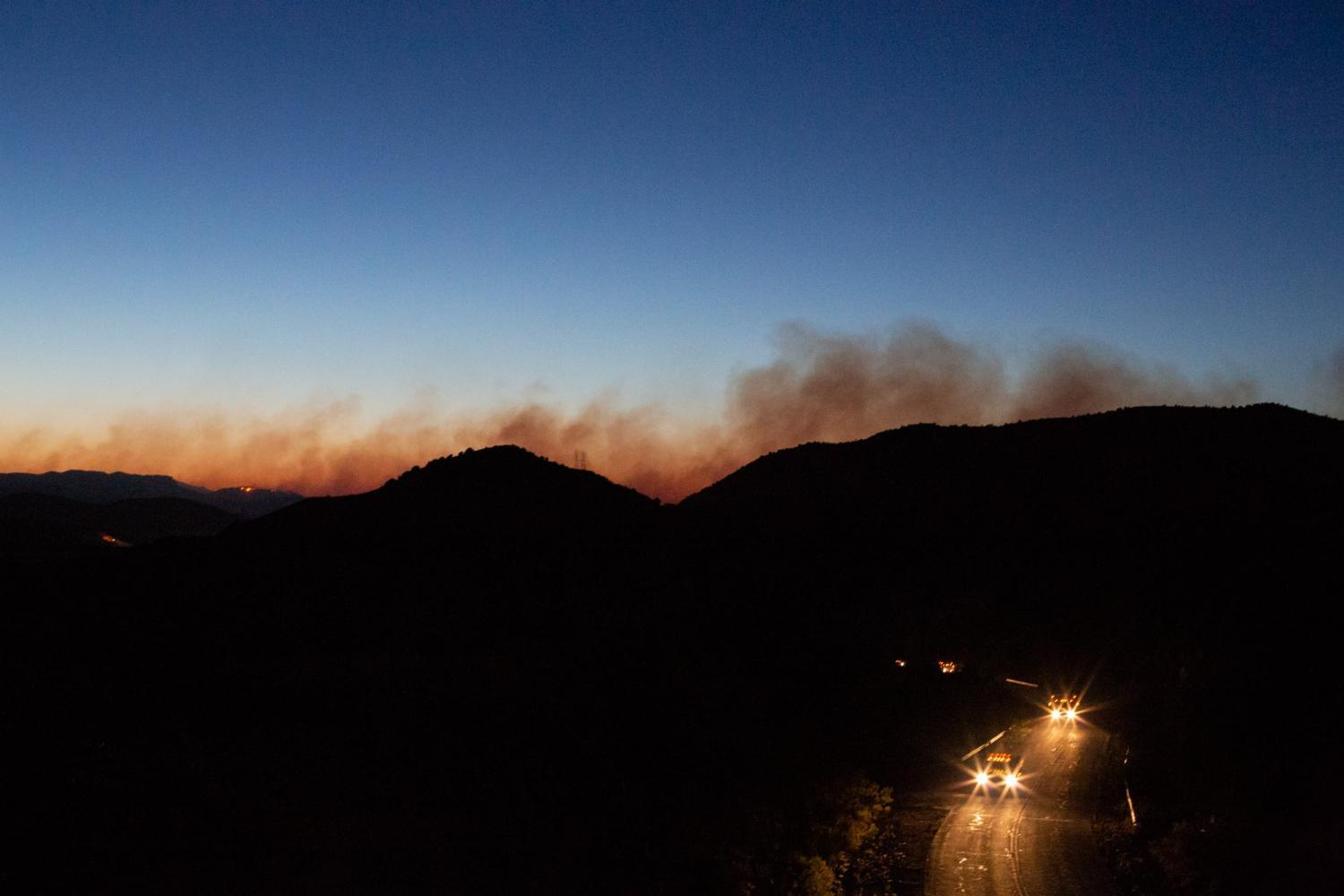 Hotshot crews return to their camps as smoke from the Woodbury Fire rises