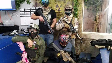 Airsoft players pose outside the field.