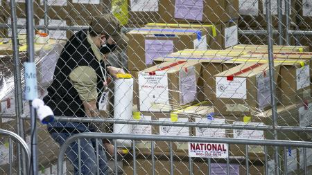 Maricopa County ballots from the 2020 general election are examined and recounted by contractors