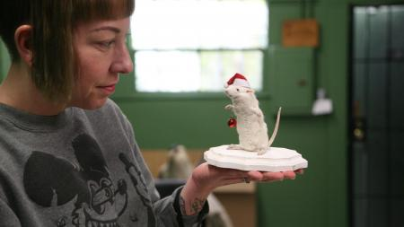Courtney Perez holds a holiday stuffed rat