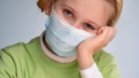 Girl sad in COVID-19 protective mask
