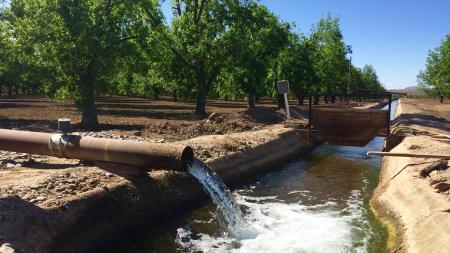 A pipe spills water pumped from an underground aquifer