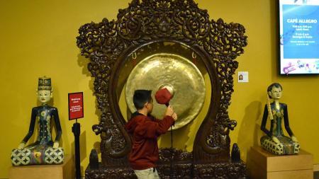 kid hits gong at the mim