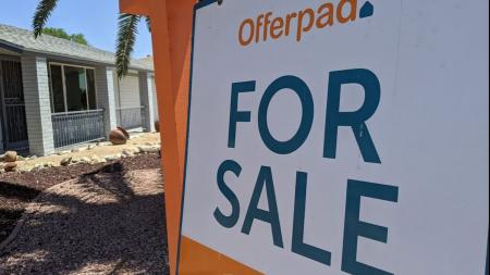 for sale sign in front of a house