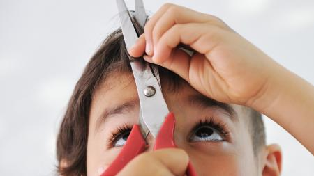 a child cutting their hair with scissors
