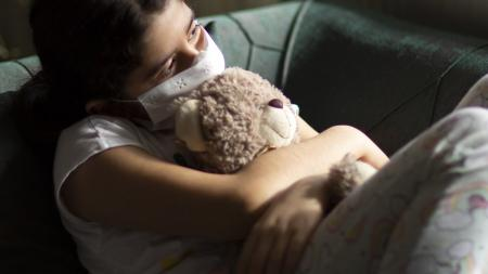 sad childing holding a stuffed bear