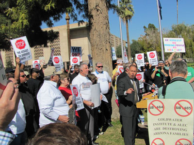 Public union members hold up signs against the anti-union bills.